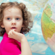 Stock Photo: Smart little girl looks closely, picture on background o