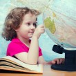 Smart little girl looks closely in globes - Stock Photo