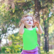 Little baby girl blowing dandelion in the park — Stock Photo