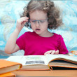 Smart little girl with glasses reading a book, square image — Stock Photo #18709467