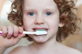 Portrait of the little girl brushing her teeth — Stock Photo