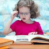 Smart little girl with glasses reading a book, square image — Stock Photo