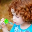 Stock Photo: A little girl blowing soap bubbles, closeup portrait beautiful
