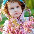 Beautiful curly-haired girl with a bouquet of spring flowers — Stock Photo