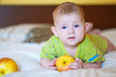 Baby lying and holding a yellow apple — Stock Photo