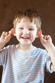 Happy Little boy, pulling himself on the ears — Stock Photo