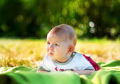 Baby on the grass in the spring park — Stock Photo