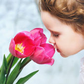 beautiful girl smelling red tulips — Stock Photo