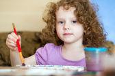 Mooie curly-haired meisje trekt — Stockfoto