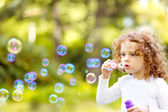 A little girl blowing soap bubbles, closeup portrait beautiful c — Stock Photo