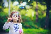 A little girl blowing soap bubbles, closeup portrait beautiful c — Stock Photo