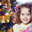 Little curly girl near the Christmas tree. — Stock Photo