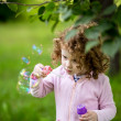 Stock Photo: A little girl blowing soap bubbles, closeup portrait beautiful c