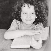Black and white portrait of girl with book, smiles wistfully. — Stock Photo