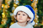Portrait of a smart kid in a blue Santa hat, close-up on New Yea — Stock Photo