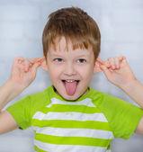 Happy Little boy, pulling himself on the ears — Stock Photo