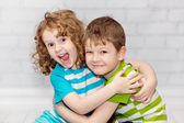 Happy brother and sister smiling and embracing. — Stock Photo