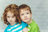 Little brother hugging sister, close-up portrait on a light back — Stock Photo