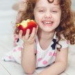 Stock Photo: Child is eating red apple