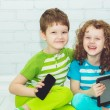 Twins boy and girls with the tablet PC on a light background. Ho — Stock Photo