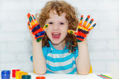 Happy little curly girl with hands in the paint on a light backg — Stock Photo