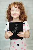 """Happy girl holding a blackboard with the text """"I love Mom"""". — Stock Photo"""
