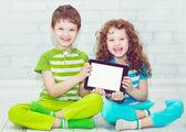 близнецы мальчик и девочки с tablet pc на светлом фоне. хо — Стоковое фото