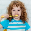 Portrait of the little girl brushing her teeth — Stock Photo #37989149