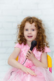 Little girl in a pink dress, singing with microphone in studio o — Stock Photo