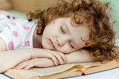 Retrato de uma menina dormindo, lendo um livro. — Fotografia Stock