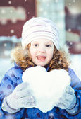 Beautiful little girl happily playing snowballs in winter park o — Stock Photo