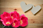 Valentine hearts and red tulips on a wooden background. — Stock Photo