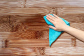 Hand with a rag to dust the wood furniture — Stock Photo