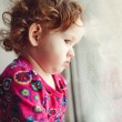 Sad little girl looking out the window. — Stock Photo #40182655