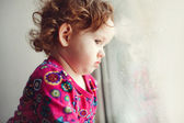 Sad little girl looking out the window. — Stock Photo