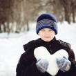 Stockfoto: Charming child holding heart shaped snow in winter park.