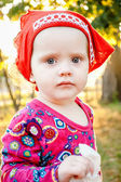 Little girl in red dress holding a handkerchief. — Stock Photo
