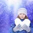 Beautiful little girl happily holding a snowball in the shape of — Stock Photo #40556161