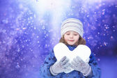 Beautiful little girl happily holding a snowball in the shape of — Stock Photo