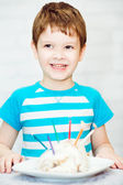 Portrait of a little boy with a cake and candles. — Stock Photo