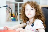 Petite fille au comptoir d'un livre de lecture — Photo