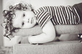 Little girl lays on a sofa. Looking into the camera. — Stock Photo