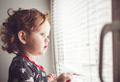 Little girl looking out the window through the blinds — Stock Photo