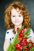 Smiling girl with red tulips in blackboard background. — Stock Photo