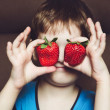 Boy holds a strawberry in hands on chocolate background. — Stock Photo