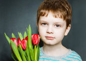 Serious boy holding a bouquet of red tulips. — Stock Photo