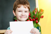 Happy boy holding a piece of paper blank and smiling on a backgr — Stock Photo