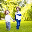 Boy and girl running holding his hand in spring park. — Stok fotoğraf