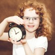 Curly girl holding alarm clock. Photo toned brown. — Stock Photo #45063759