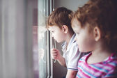 Little kids looking out the window. — Stock Photo